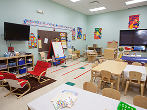 Colorful daycare room featuring tvs, tables, and activities