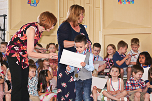 Handing out preschool graduation diploma