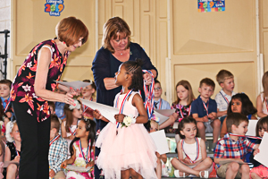 Happy girl receiving preschool diploma