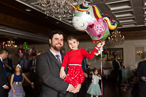 Father and daughter posing with a balloon animal