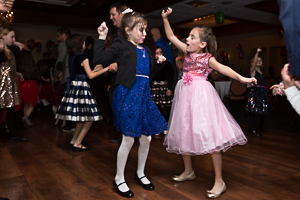 Two girls dancing together in dresses