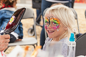 Happy kid getting face painted