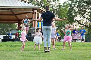 Kids dancing at a concert in the park