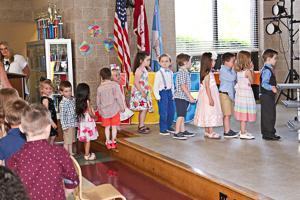 Preschool graduates walking on stage