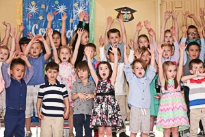 Crowd celebrating preschool graduation