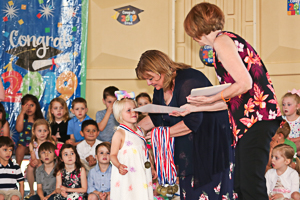 Preschool graduate receiving diploma